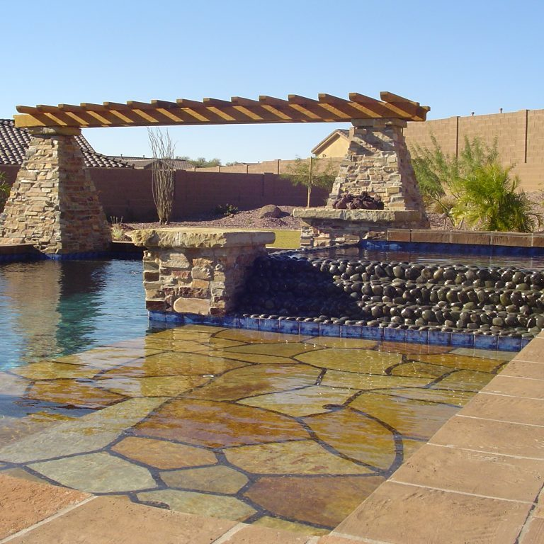 Pool with stone, stone waterfall, and stone pilars with wooden pergola